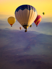 Multicolored Hot air balloons flying over mountains peaks at sunrise. Travel concept with ballooning, golden sunlight and morning haze for your vertical poster about adventures or dreams.