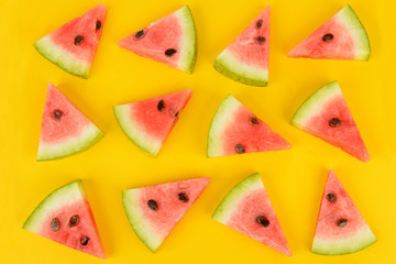 Sliced ripe watermelon on a bright yellow background. Flat lay, top view.