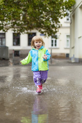 Kleines Kind läuft in Regen durch Wasser Lacke. Little child girl running happy trough puddle.