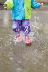 Kleines Kind läuft mit Gummistiefeln durch Wasser / Pfütze. Little child running trough puddle with rubber boots.