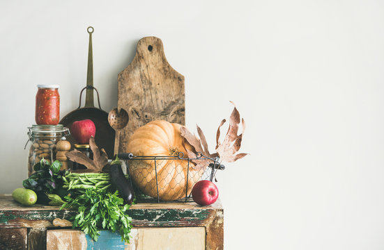 Autumn seasonal food ingredients and kitchen utensils. Vegetables, pumpkin, apples, canned food, fallen leaves over rustic chest of cupboard, copy space. Thanksgiving dinner preparation