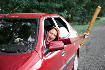 young female driver has stress and anger, threatens with a baseball bat, has a red car