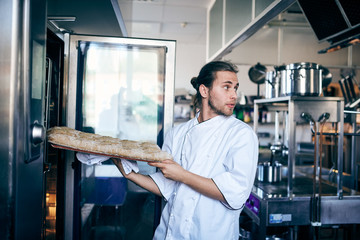 Male chef putting bread in oven while looking away at commercial kitchen
