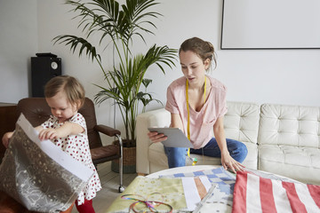Fashion designer with digital tablet examining textile while daughter playing at home