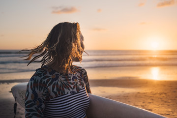 Female surfer with surfboard looking at sea during sunset at beach