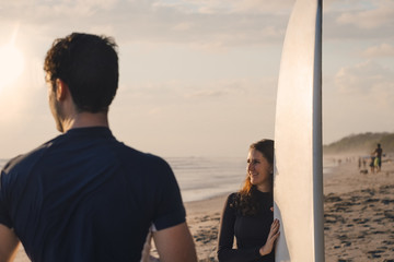 Young man with female friend holding surfboard at beach during sunset