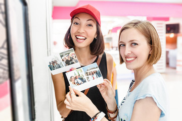 Two happy girls friends looking at instantly printed photographs in an automated self-service machine terminal for printing photos from a smartphone or the Internet