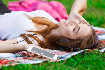 Cute teenage girl in white t-shirt with headphones lies on the green grass with closed eyes in summer park