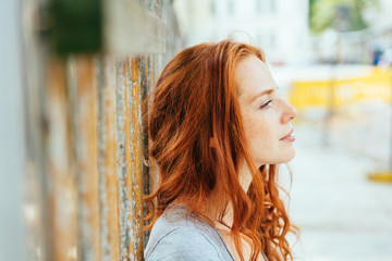 Thoughtful young woman with tousled red hair