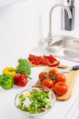 delicious tomatoes and chili peppers on cutting boards in light kitchen