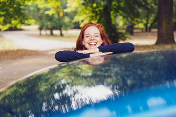 Laughing young woman leaning on a blue car