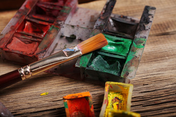Artistic paintbrushes and watercolor paint  on the old wooden background
