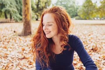 Woman relaxing in a park smiling with pleasure