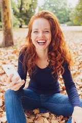 Vivacious laughing young woman in an autumn park