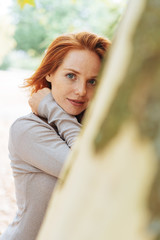 Young redhead woman smiling quietly at the camera