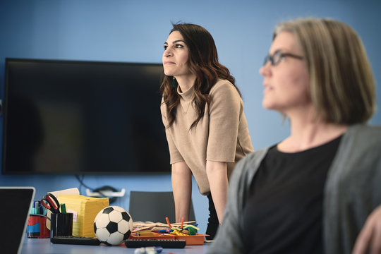 Mature female engineer looking away while standing by colleague at table in office