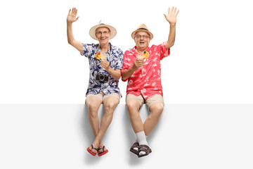 Two cheerfull seniors holding cocktails and waving