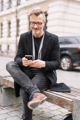 Stylish man seated on a city bench using a mobile