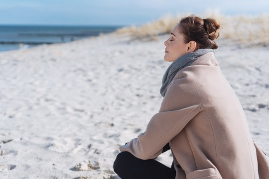 Young woman relaxing at the seaside in winter