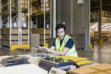 Confident young male customer service representative using laptop while sitting at desk in warehouse