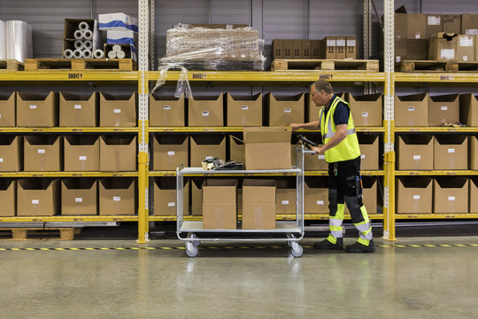 Full length side view of senior male worker pushing cart with cardboard boxes by rack at distribution warehouse