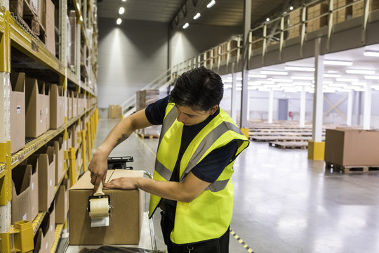 Young male worker packing cardboard box with adhesive tape at distribution warehouse