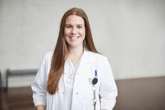 Portrait of smiling young female brunette doctor standing in corridor at hospital