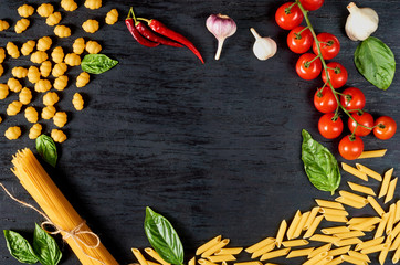 Frame of Italian traditional food, spices and ingredients for cooking as basil, cherry tomatoes, chili pepper, garlic and various pasta on black wooden background. Top view with space for text