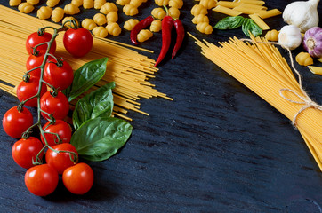 Italian traditional food, spices and ingredients for cooking: basil leaves, cherry tomatoes, garlic, chili pepper and various pasta on black wooden background. Side view with space for text