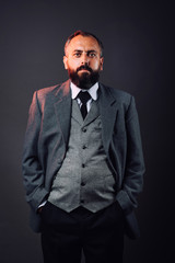 Portrait of bearded man dressed in strict suit looking forward on black background
