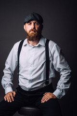 Bearded man in hat and suspenders on the black background