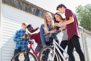 Group Of Teenage Friends On Bikes Looking At Mobile Phones