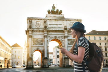 A tourist girl with a backpack looks sights in Munich in Germany. Passes by the triumphal arch. Wall mural