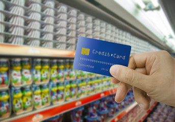 Supermarket aisle and male hand holding credit card