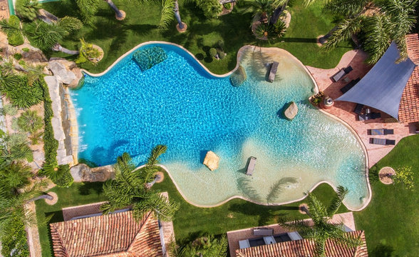 Original decorative pool in the garden with palm trees, aerial view.