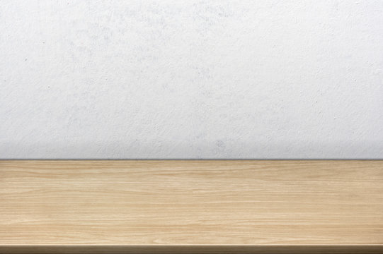 Empty wooden desk table near a textured wall