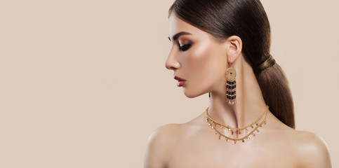 Elegant woman with fashion jewelry on pink background. Gold jewelry for woman, necklace and earrings with black gemstones. Beauty and accessories.