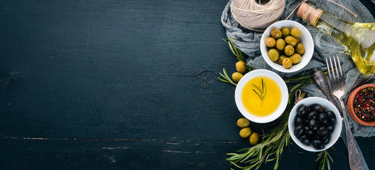 A set of olives and olive oil and rosemary. Green olives and black olives. On a black wooden background. Free space for text. Wall mural