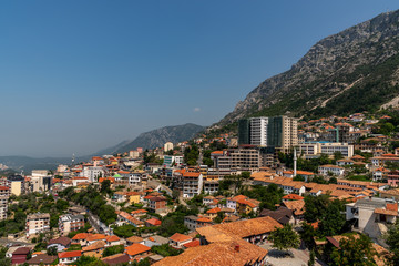 Scenic landscape view of the city Kruja on a mountain slope with blue sky in Albania.