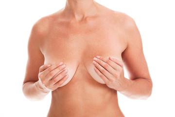 Naked woman covers her breasts by hands, isolated on white background