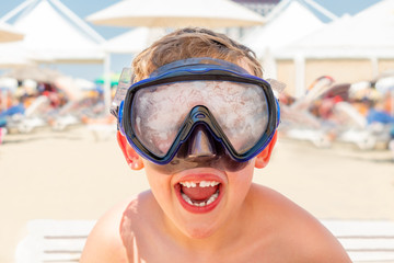 Closeup portrait of a happy laughing boy with diving mask at a sunny beach.