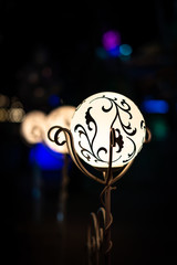 Night view of bright vintage lamp lantern with decoration. Selective focus with soft bokeh.