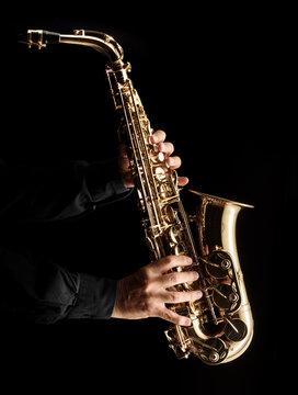Musician playing alt saxophone on black