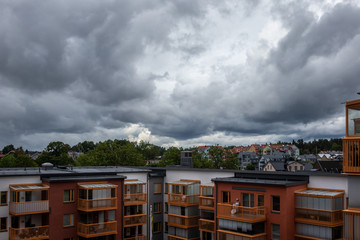 Dark summer  storm clouds over residential city buildings and rooftops.