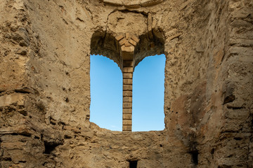 Inside of ancient stone brick ruin building with arched window and blue sky.