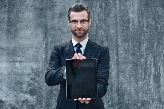 Smiling successful young businessman on a concrete background in a classic suit and tie presents a tablet