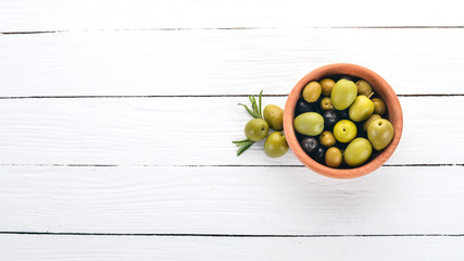 Wall Mural - Olives in a plate and rosemary. On a white wooden background. Free space for text.