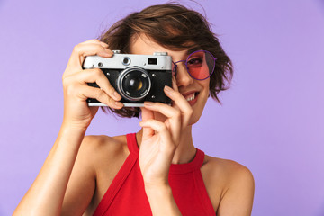 Photo of hipster girl 20s in sunglasses smiling and taking photo on retro camera, isolated over violet background