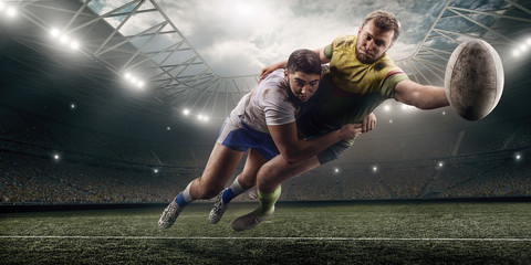 Two male Rugby players fight for the ball in flight on professional rugby stadium Wall mural