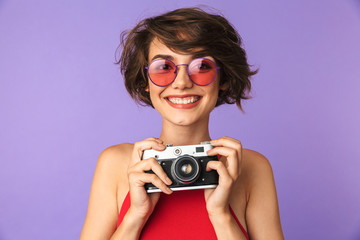 Wall Mural - Photo of trendy girl 20s in sunglasses smiling and taking photo on retro camera, isolated over violet background